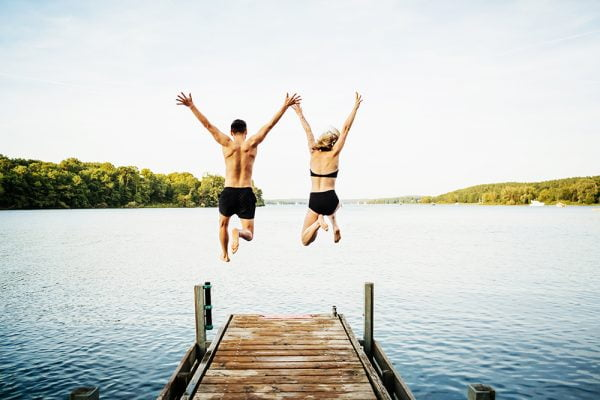 two happy-looking people in swimsuits jumping off dock into lake