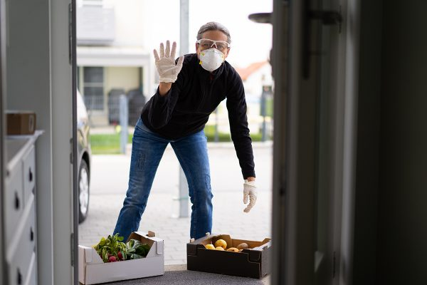 man delivering produce wearing gloves and face mask