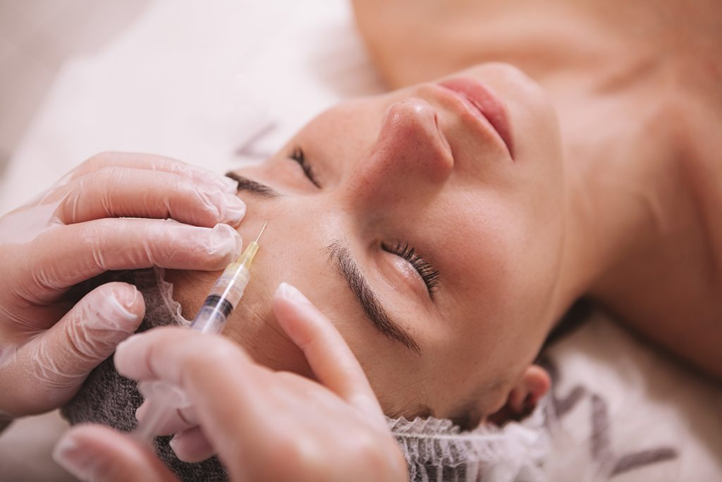reclined person receives botox injection between the eyebrows
