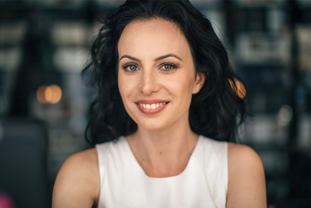 smiling brunette with rejuvenated eyebrows after botox