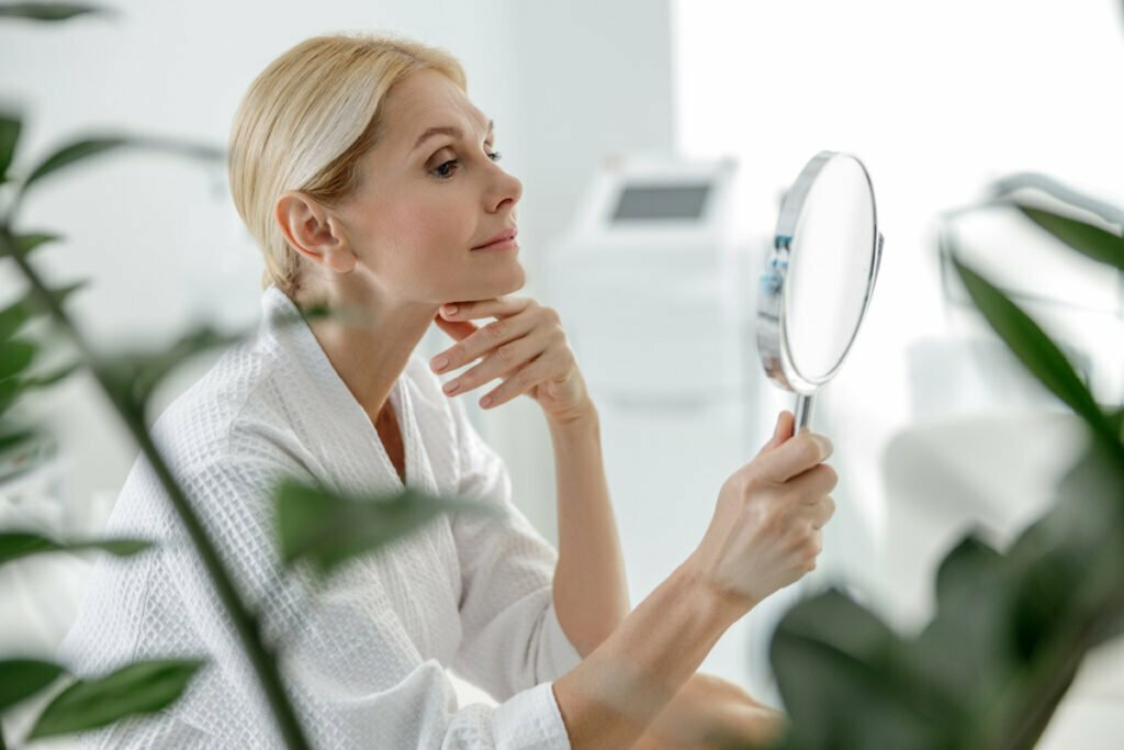 Mature woman examines face and neck in mirror