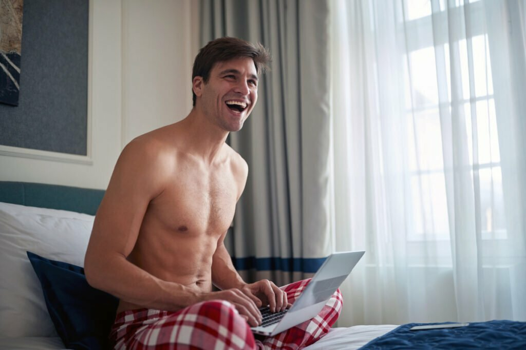 Shirtless man on bed with laptop
